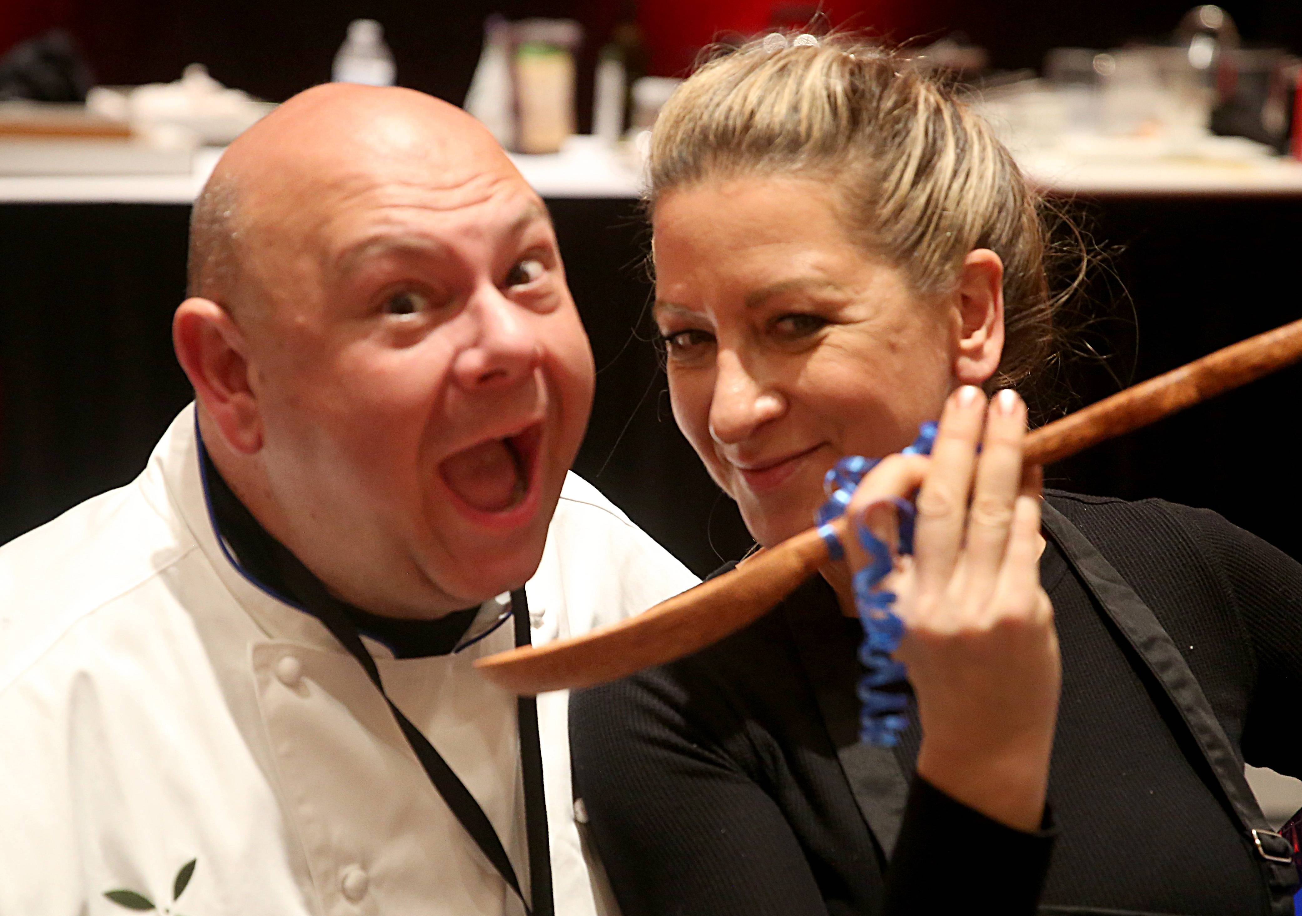 Winner Darla Pitts of Chicago, right, celebrates with her spoon trophy and contest judge Jimmy Nicolau of Grecian Delight Foods at the conclusion of the Daily Herald Cook of the Week Challenge Finale Monday night at Westin Chicago Northwest in Itasca.