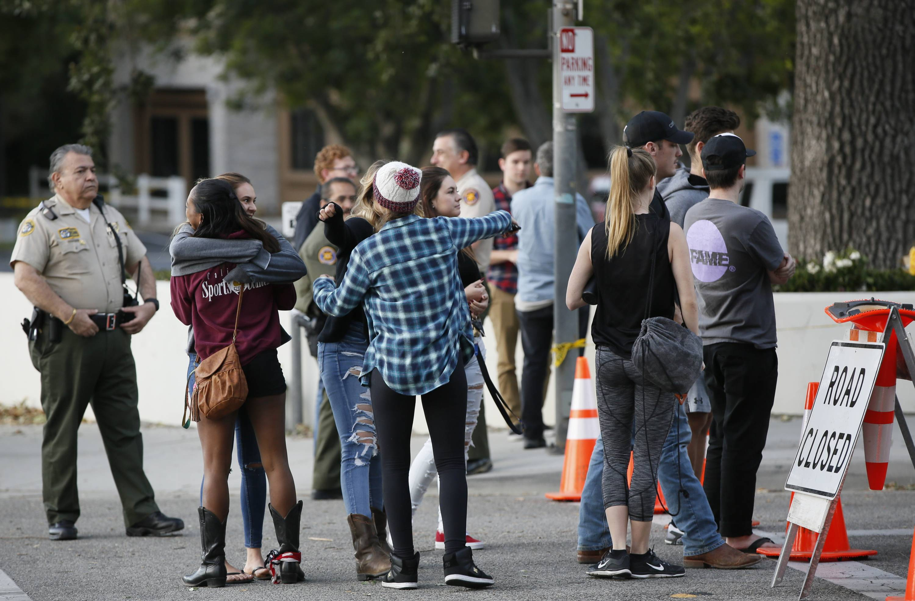 People hug Friday as they arrive to recover their vehicles parked in the parking lot the Borderline Bar & Grill bar in Thousand Oaks, California.