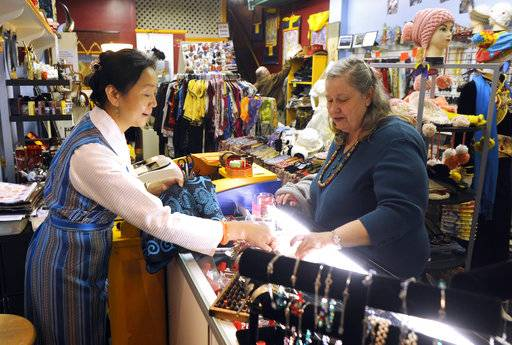 FILE- In this Nov. 24, 2012, file photo Ping's Tibet shop owner Ping Wu Longval, left, in Cotton Exchange shopping center, helps local costumer Sherry Rhodes with her shopping in Wilmington, N.C., during Small Business Saturday. Many small and independent retailers who are holding Small Business Saturday shopping events Thanksgiving weekend are banding together with others, believing that there's strength in numbers. (Jeff Janowski/The Star-News via AP)
