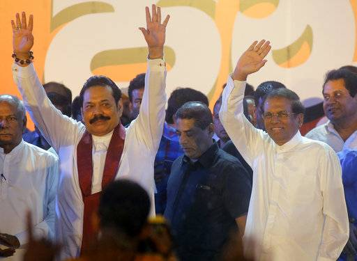 FILE- In this Monday, Nov. 5, 2018, file photo, Sri Lankan president Maithripala Sirisena, right, and his newly appointed prime minister Mahinda Rajapaksa wave to supporters during a rally held out side the parliamentary complex in Colombo, Sri Lanka. Sri Lankan is in the midst of a political crisis set off by the president's decisions to remove the South Asian island nation's prime minister, dissolve Parliament and call snap elections. The moves have triggered public protests and international criticism, including from some of the country's biggest donors. (AP Photo/Eranga Jayawardena, file)