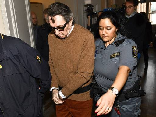 Frenchman Jean-Claude Arnault is escorted from court after the first day of his appeal trial, in Stockholm, Monday, Nov. 12, 2018. Arnault, a major cultural figure in Sweden and the husband of former Swedish Academy member Katarina Frostenson was convicted of rape in October and sentenced to two years in prison. (Jonas Ekstromer/TT News Agency via AP)