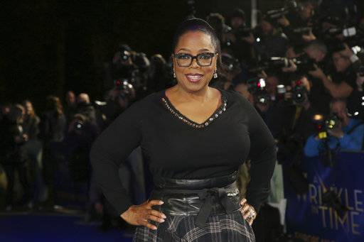 "FILE - In this March 13, 2018, file photo, actress Oprah Winfrey poses for photographers upon arrival at the premiere of the film 'A Wrinkle In Time' in London. Winfrey has chosen Michelle Obama's ""Becoming� as her next book club pick, The Associated Press has learned. In a statement Monday, Nov. 12, Winfrey said the memoir was ""well-written� and inspirational. (Photo by Joel C Ryan/Invision/AP, File)"