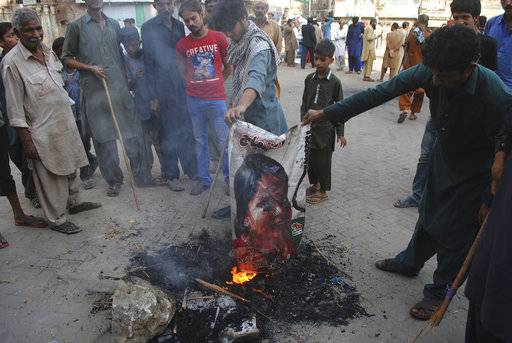 "FILE - In this Nov. 1, 2018, file photo, Pakistani protesters burn a poster image of Christian woman Aasia Bibi, in Hyderabad, Pakistan. Pakistan's government struggling with a crisis surrounding Bibi - a Christian woman acquitted of blasphemy charges after eight years on death row - now has to deal with ""fake"" images on social media purporting to show her leaving the country. (AP Photo/Pervez Masih, File)"