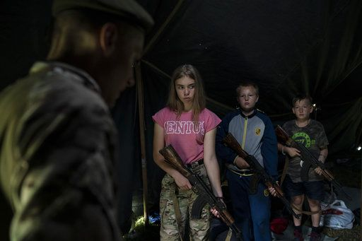 "In this July 28, 2018 photo, participants of the ""Temper of will"" summer camp, organized by the nationalist Svoboda party, hold their AK-47 riffles as they receive instructions during a tactical exercise in a village near Ternopil, Ukraine. Campers as young as 8 years old practice using assault rifles. They are taught to shoot to kill Russians and their sympathizers."