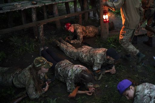 "In this July 28, 2018 photo, young participants of the ""Temper of will"" summer camp, organized by the nationalist Svoboda party, hold a plank position before having dinner in a village near Ternopil, Ukraine."