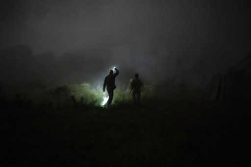"In this July 29, 2018 photo, instructor Georgiy Barylenko, left, holds a flashlight as he walks with a young participant of the ""Temper of will"" summer camp, organized by the nationalist Svoboda party, during a night drill in a village near Ternopil, Ukraine."