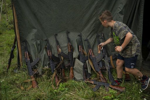 "In this July 28, 2018 photo, a young participant of the ""Temper of will"" summer camp, organized by the nationalist Svoboda party, grabs his AK-47 during a tactical exercise in a village near Ternopil, Ukraine. ""We never aim guns at people,"" instructor Yuri ""Chornota"" Cherkashin tells campers. ""But we don't count separatists, little green men, occupiers from Moscow as people, so we can and should aim at them."""