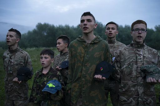 "In this July 28, 2018 photo, Mykhailo, 18, center, leads other young participants of the ""Temper of will"" summer camp, organized by the nationalist Svoboda party, as they stand in formation singing nationalist songs in a village near Ternopil, Ukraine. Mykhailo is the oldest of the campers. ""Every moment things can go wrong in our country. And one has to be ready for it,"" he said. ""That's why I came to this camp. To study how to protect myself and my loved ones."""