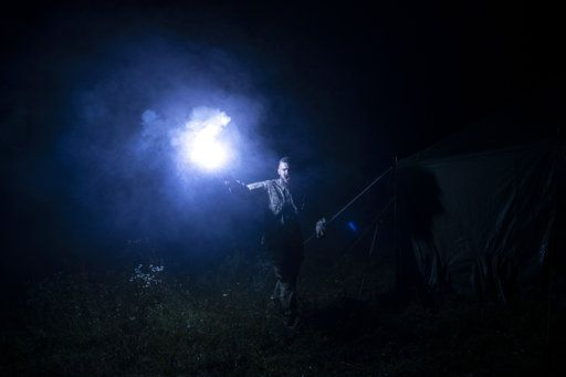 "In this July 29, 2018 photo, instructor Georgiy Barylenko, holds a flare as he instructs young participants of the ""Temper of will"" summer camp, organized by the nationalist Svoboda party, during a night drill in a village near Ternopil, Ukraine."