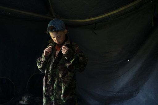 "In this July 27, 2018 photo, a young participant of the ""Temper of will"" summer camp, organized by the nationalist Svoboda party, buttons up a camouflage shirt as he prepares for an exercise in a village near Ternopil, Ukraine. Campers as young as 8 years old practice using assault rifles. They are taught to shoot to kill Russians and their sympathizers."