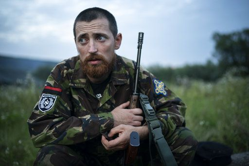 "In this July 29, 2018 photo, Yuri ""Chornota"" Cherkashin, head of Sokil (Falcon), the youth wing of the nationalist Svoboda party, sits with his AK-47 rifle at the ""Temper of will"" summer camp in a village near Ternopil, Ukraine. ""We never aim guns at people,"" he tells his campers. ""But we don't count separatists, little green men, occupiers from Moscow as people, so we can and should aim at them."""