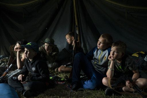 "In this July 28, 2018 photo, young participants of the ""Temper of will"" summer camp, organized by the nationalist Svoboda party, sit inside a tent with their AK-47 riffles as they receive instructions during a tactical exercise in a village near Ternopil, Ukraine. The camp has two purposes: to train children to defend their country _ and to spread nationalist ideology."
