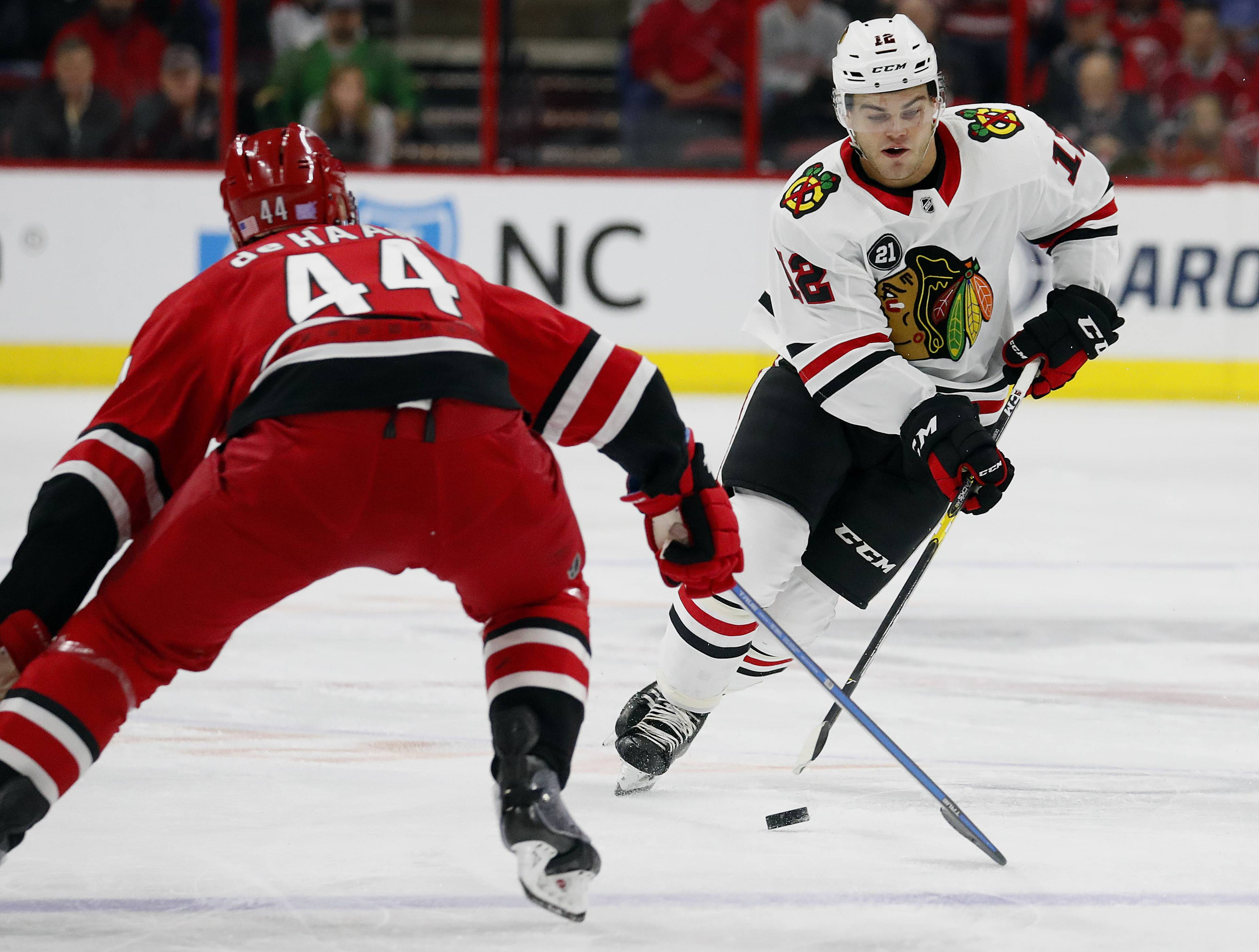 Chicago Blackhawks' Alex DeBrincat (12) moves the puck on Carolina Hurricanes' Calvin de Haan (44) during the first period of an NHL hockey game, Monday, Nov. 12, 2018, in Raleigh, N.C. (AP Photo/Karl B DeBlaker)