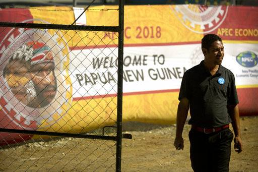 A worker passes by a banner at the APEC 2018 International Media Center at Port Moresby, Papua New Guinea Wednesday, Nov. 14, 2018. After three decades of promoting free trade as a panacea to poverty, the APEC grouping of nations that includes the U.S. and China is holding its lavish annual leaders meeting in the country that can least afford it. (AP Photo/Aaron Favila)