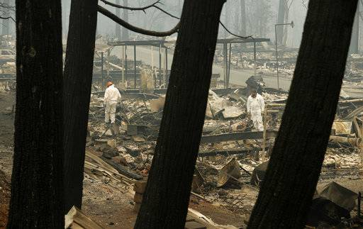 A search and rescue workers search for human remains at a burned out trailer park from the Camp fire, Tuesday, Nov. 13, 2018, in Paradise, Calif. The deadliest, most destructive blaze in California history has killed multiple people. (AP Photo/John Locher)