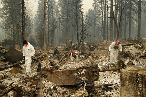 Search and rescue workers search for human remains at a trailer park burned by the Camp Fire, Tuesday, Nov. 13, 2018, in Paradise, Calif. (AP Photo/John Locher)