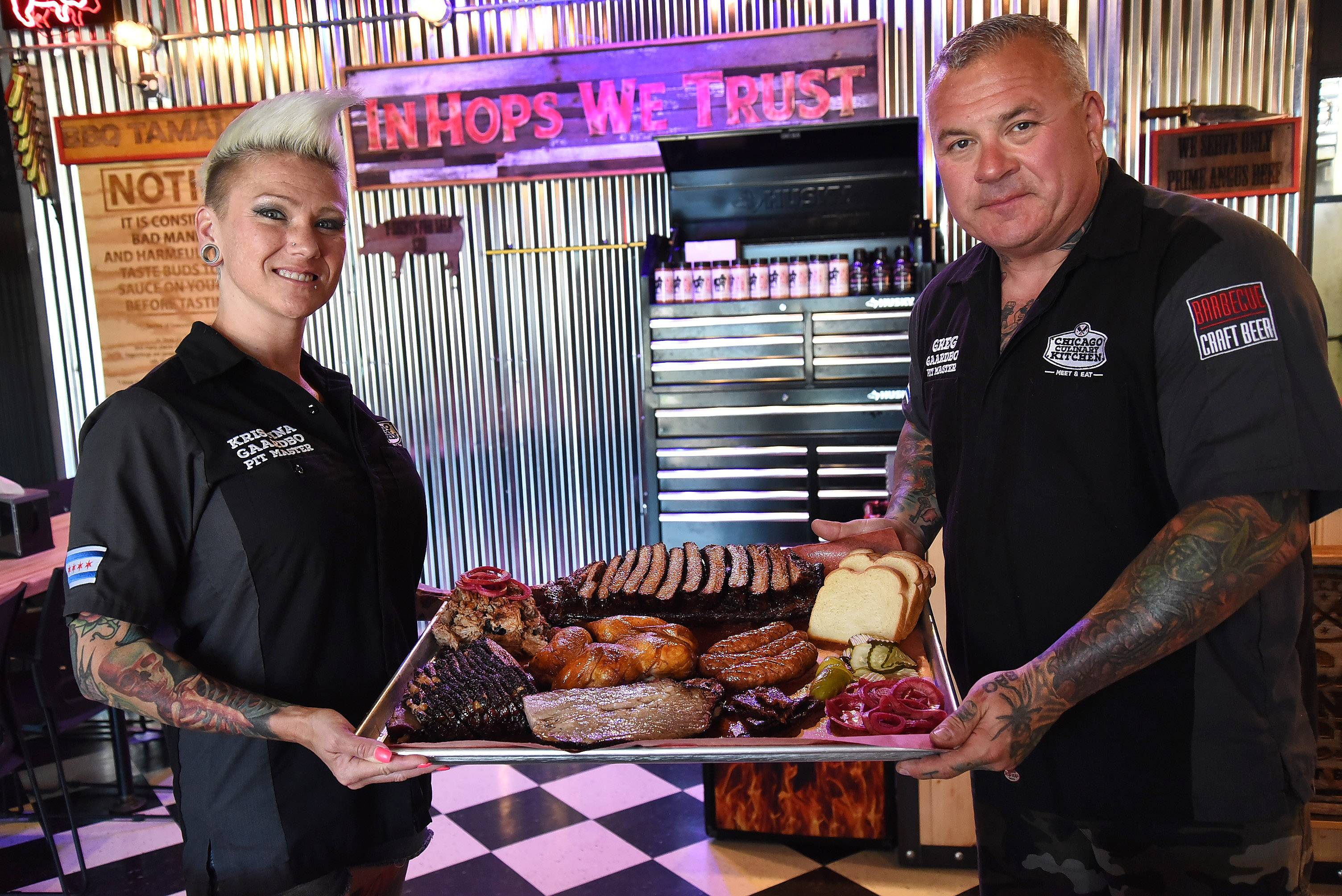 "Palatine's Chicago Culinary Kitchen will be one of the restaurants reviewed Friday night on ""Check, Please!"" The show airs at 8 p.m. on WTTW-Channel 11. Here, co-owners Greg and Kristina Gaardbo hold a platter of barbecue."