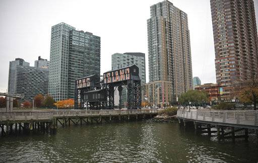 "A former dock facility is shown with old transfer bridges, with ""Long Island"" painted in large letters at Gantry State Park in the Long Island City section of Queens, N.Y., Tuesday Nov. 13, 2018, in New York. Amazon announced Tuesday it has selected the Queens neighborhood as one of two sites for its headquarters. (AP Photo/Bebeto Matthews)"