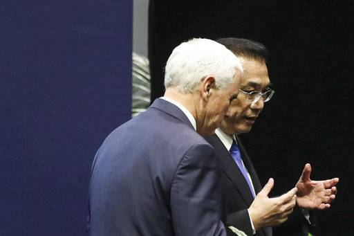 U.S. Vice President Mike Pence, left, and Chinese Premier Li Keqiang interact on stage after a group photo during the 13th East Asian Summit Plenary on the sidelines of the 33rd ASEAN summit in Singapore, Thursday, Nov. 15, 2018. (AP Photo/Yong Teck Lim)