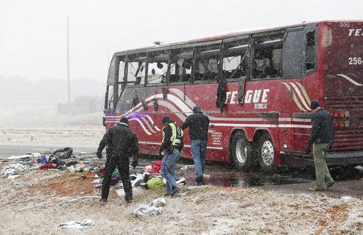 Law enforcement officers inspect the site where a tour bus carrying passengers overturned just after midday, Wednesday, Nov. 14, 2018, in DeSoto County, Miss. The crash came as a winter storm has been raking parts of the South. (Joe Rondone/The Commercial Appeal via AP)