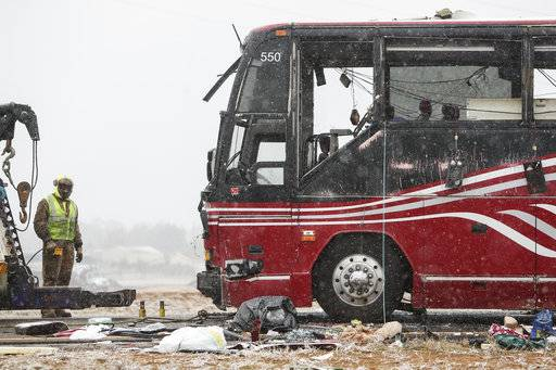 A towing service employee inspects the damage to a tour bus carrying passengers, that overturned just after midday Wednesday, Nov. 14, 2018, in DeSoto County, Miss. The crash came as a winter storm has been raking parts of the South. (Joe Rondone/The Commercial Appeal, via AP)