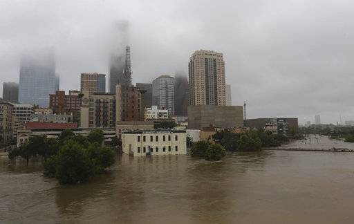 FILE - In this Monday, Aug. 28, 2017 file photo, floodwaters from Tropical Storm Harvey overflow from Buffalo Bayou in downtown Houston, Texas. A study released on Wednesday, Nov. 14, 2018 says that between being tripped up by downtown and the bigger effect of massive paving and building up of the metro area to reduce drainage, development in Houston on average increased the extreme flooding risk by 21 times. (AP Photo/LM Otero)