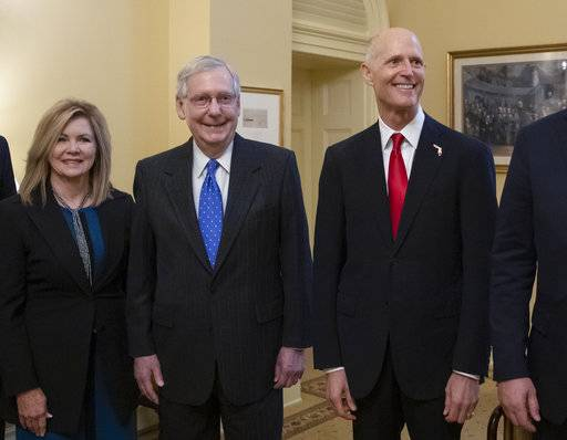 Senate Majority Leader Mitch McConnell, R-Ky., center, is flanked by Rep. Marsha Blackburn, R-Tenn., left, the senator-elect from Tennessee, and Florida Gov. Rick Scott, the Republican candidate in the undecided challenge to incumbent Sen. Bill Nelson, D-Fla., during a meeting with new GOP senators at the Capitol in Washington, Wednesday, Nov. 14, 2018. (AP Photo/J. Scott Applewhite)