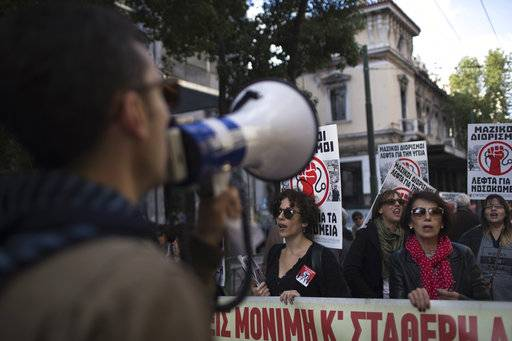 "State hospital workers chant slogans as they hold placards which read in Greek. ""Money for hospitals"" during a protest in central Athens, on Wednesday, Nov. 14, 2018. Civil servants in Greece have walked off the job in a 24-hour strike to protest austerity measures and are demanding wage and pension increases as well as the abolition of all legislation imposed as part of the country's international bailouts. (AP Photo/Petros Giannakouris)"