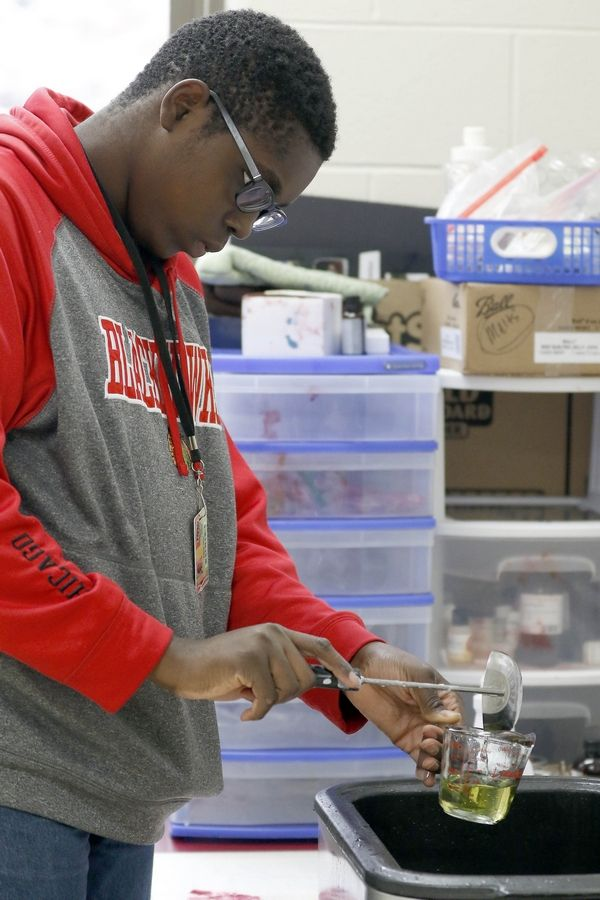 "Elijah Onu, 17, measures wax during a candle-making class Thursday at Huntley High School. Special education students in the school's job skills program will sell ""EdSpecial Scents"" candles Saturday at the Leggee Elementary Holiday Craft Fair."