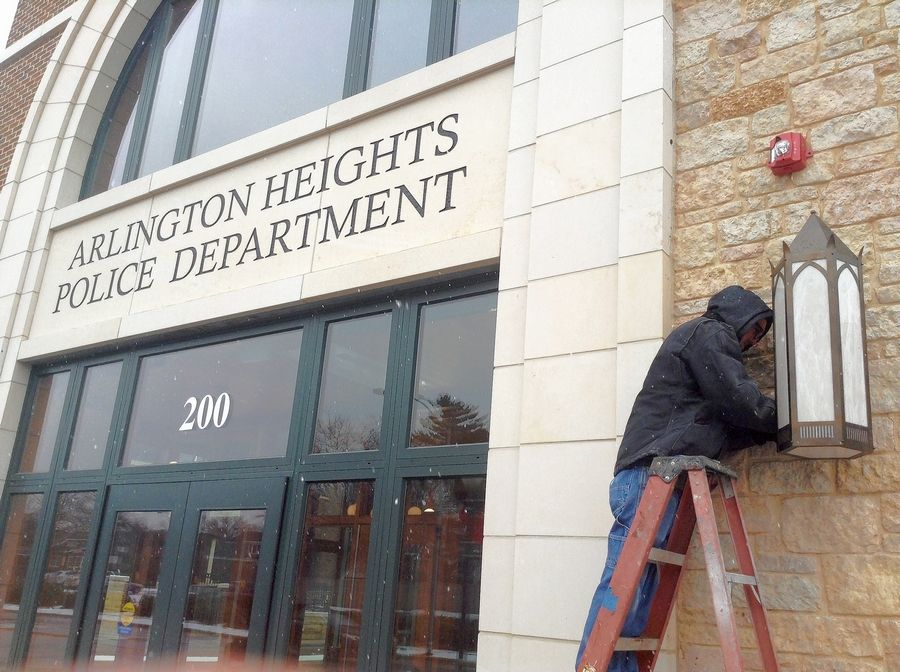 A worker on Thursday reinstalls lighting outside the new Arlington Heights police station, where a car crashed into the lobby wall Sunday.