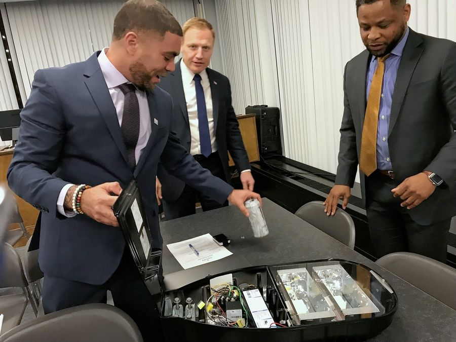 Elgin Public Works Superintendent Aaron Neal, left, shows an LED light to Councilman Toby Shaw, center, after a city council meeting Wednesday. On the right is Rod Young of The Will Group based in Chicago, which made the light.