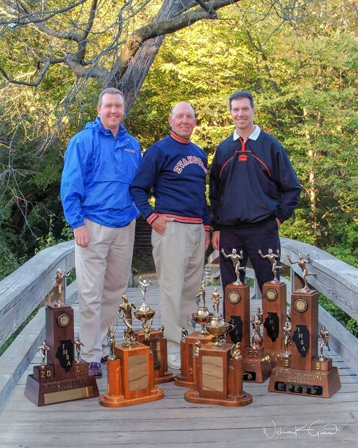Standing with their state track and field trophies are Ron Helberg flanked by his sons, Don Helberg (left) of Wheaton North, and retired Wheaton Warrenville South coach Ken Helberg.