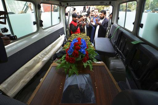 Nangarhar officials hand over the body of Tahir Khan Dawar, a Pakistani police officer, to Pakistani tribal elders in the city of Jalalabad, east of Kabul, Afghanistan, Thursday, Nov. 15, 2018. Pakistan's foreign ministry and the Afghan ambassador have confirmed that the body of a Pakistani police officer who went missing in Islamabad last month has been found in neighboring Afghanistan. Dawar disappeared on Oct. 27 and was presumed abducted by militants. (AP Photo/Mohammad Anwar Danishyar)