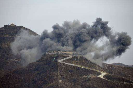This general view shows an explosion as part of the dismantling of a South Korean guard post in the Demilitarized Zone dividing the two Koreas in Cheorwon on Thursday, Nov. 15, 2018, as a North Korean guard post sits high in the upper left. (Jung Yeon-je/Pool Photo via AP)