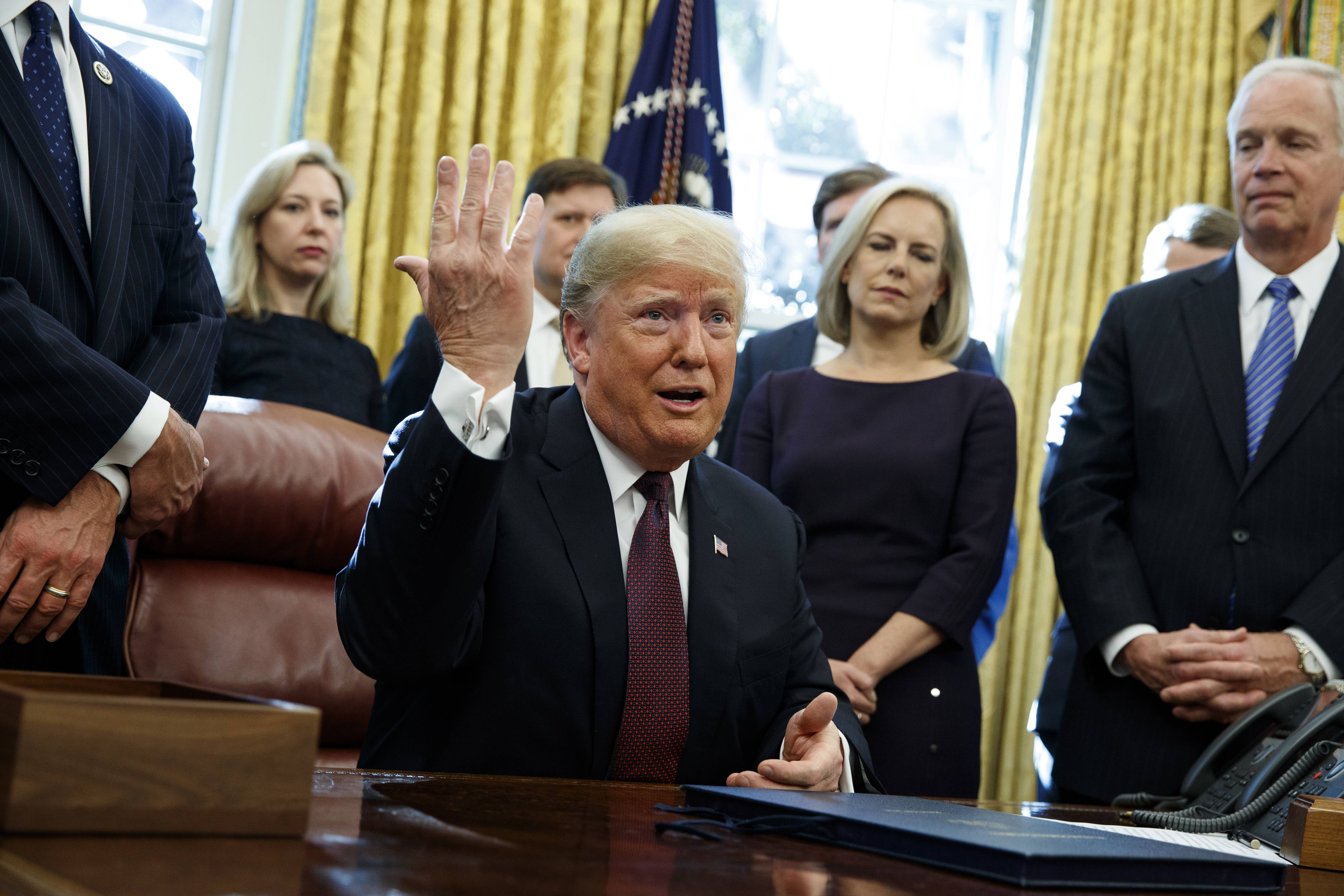 "President Donald Trump answers a reporters question about the investigation of special counsel Robert Mueller during a signing ceremony of the ""Cybersecurity and Infrastructure Security Agency Act,"" in the Oval Office of the White House, Friday, Nov. 16, 2018, in Washington. (AP Photo/Evan Vucci)"