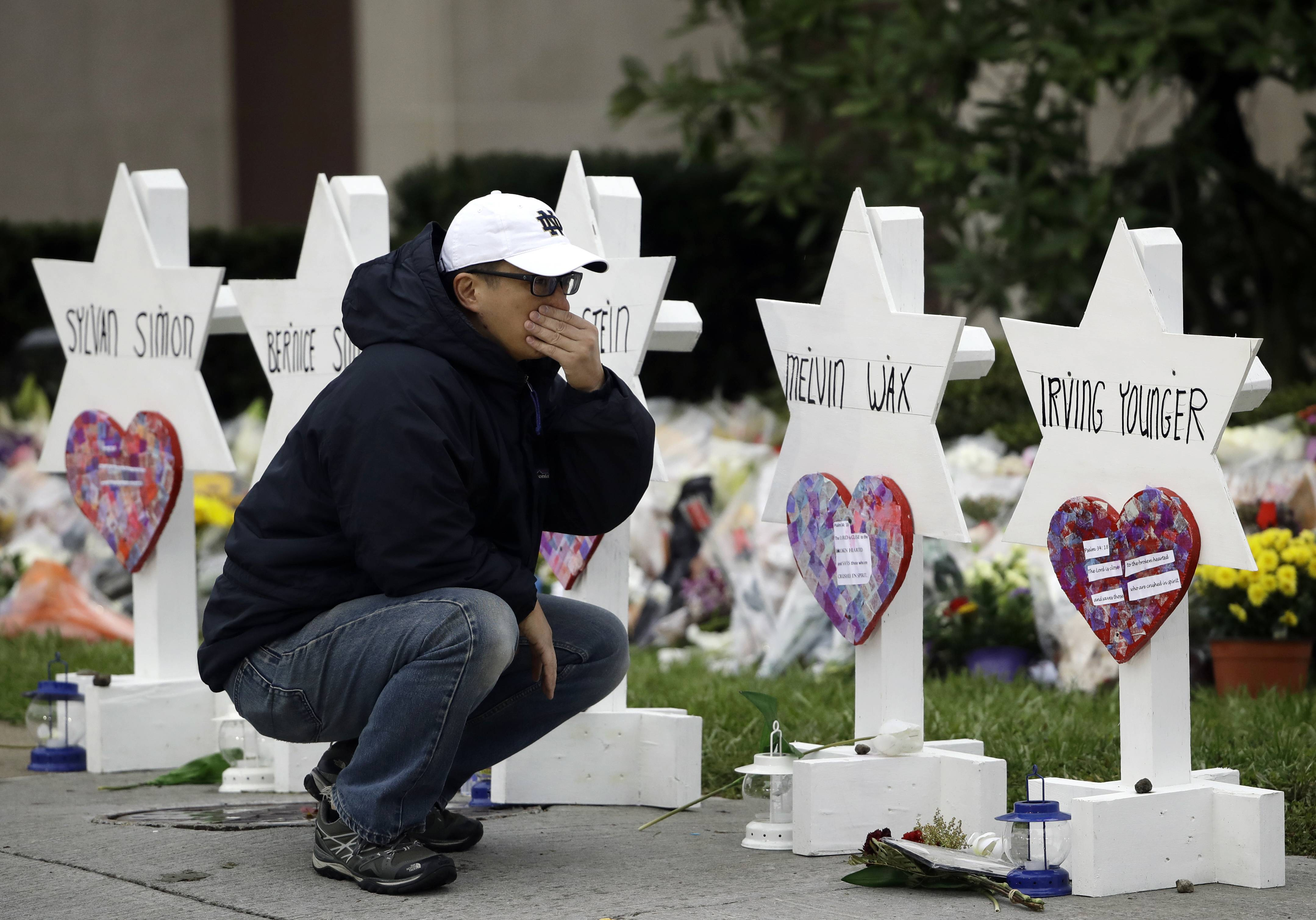 A mourner pauses in front of Stars of David with the names of those killed in the deadly shooting last month at the Tree of Life Synagogue in Pittsburgh. Even before the attack, hate crimes were on the rise in the U.S., according to an FBI report issued Tuesday. Illinois and the suburbs saw an overall decline, but the number of offenses motivated by religious hate grew.
