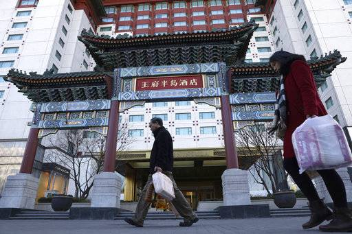 Residents passes by The Peninsula hotel which announced that it was investigating claims in an online video that supposedly showed the hotel cleaners using dirty towels to wipe cups and sinks in Beijing Friday, Nov. 16, 2018. The Chinese tourism ministry asked authorities in Beijing, Shanghai and three provinces to investigate room cleaning at 14 major hotels after hidden camera video showed workers using used towels to clean cups and glasses and other questionable practices. (AP Photo/Ng Han Guan)
