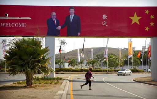 In this Nov. 15, 2018, photo, a woman crosses the street near a billboard commemorating the state visit of Chinese President Xi Jinping in Port Moresby, Papua New Guinea. As world leaders arrive in Papua New Guinea for a Pacific Rim summit, the welcome mat is especially big for China's President Xi Jinping. With both actions and words, Xi has a compelling message for the South Pacific's fragile island states, long both propped up and pushed around by U.S. ally Australia: they now have a choice of benefactors. (AP Photo/Mark Schiefelbein)