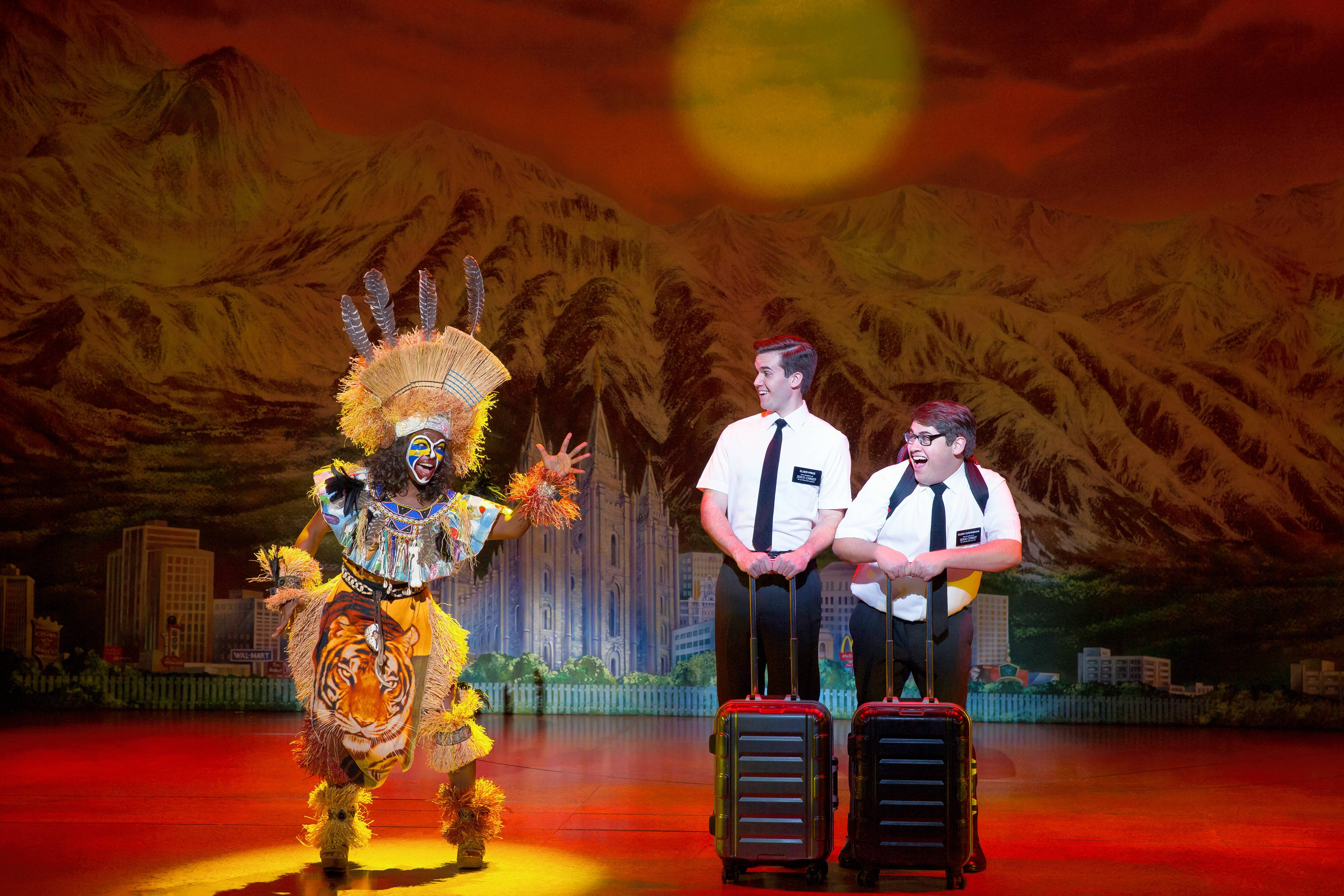 "Mrs. Brown (Monica L. Patton), left, offers a mission send off to Elder Price (Kevin Clay) and Elder Cunningham (Conner Peirson) in ""The Book of Mormon."" The national tour returns to Chicago at the Oriental Theatre from Nov. 20 to Dec. 2."