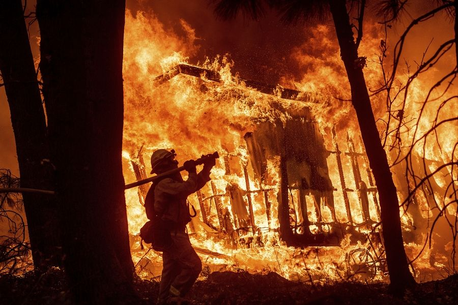 Firefighter Jose Corona sprays water as flames from the Camp Fire consume a home in Magalia, California.