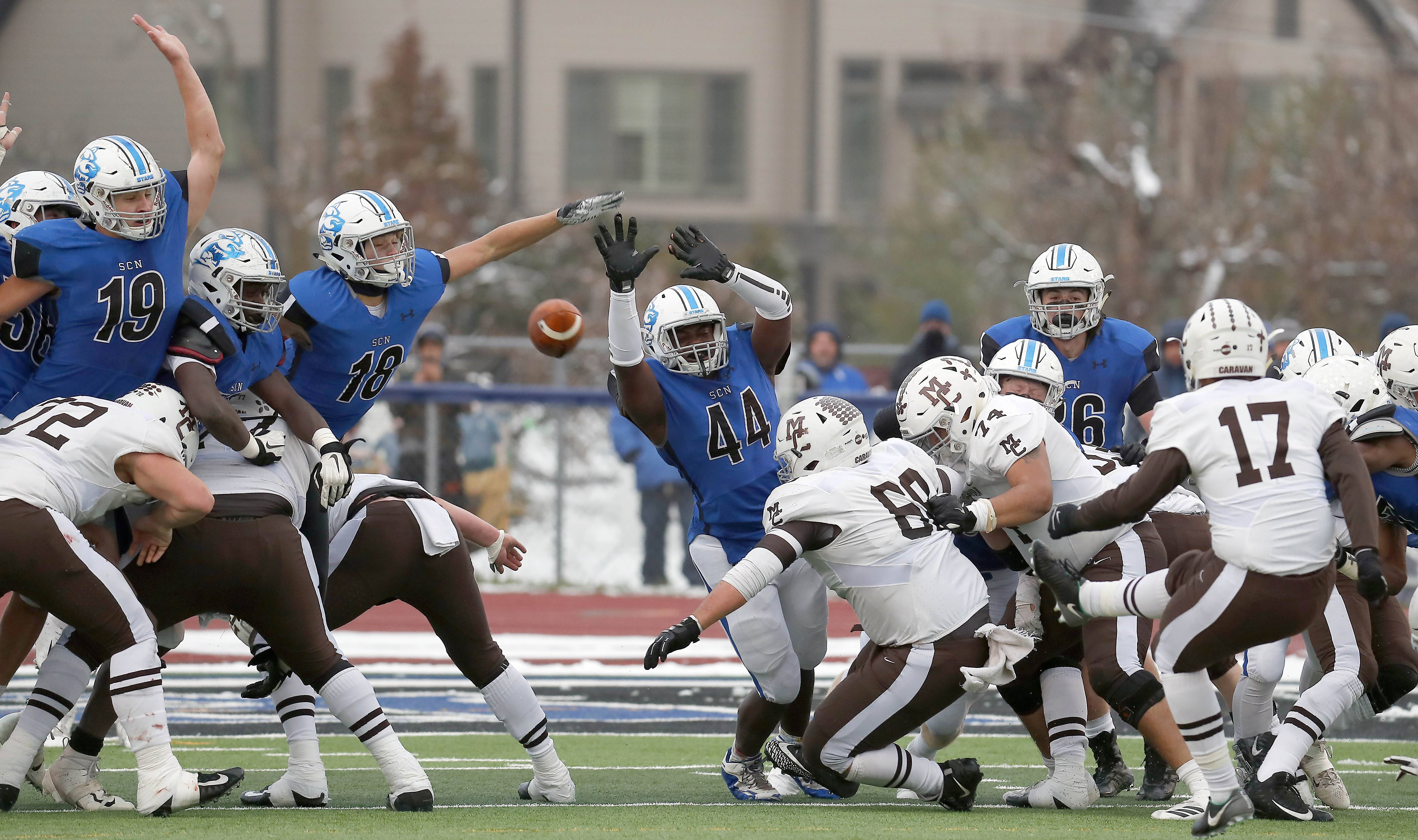 St. Charles North's DJ Oshin (44) comes up with a huge field goal block to force overtime Saturday during the IHSA Class 7A football semifinals in St. Charles.