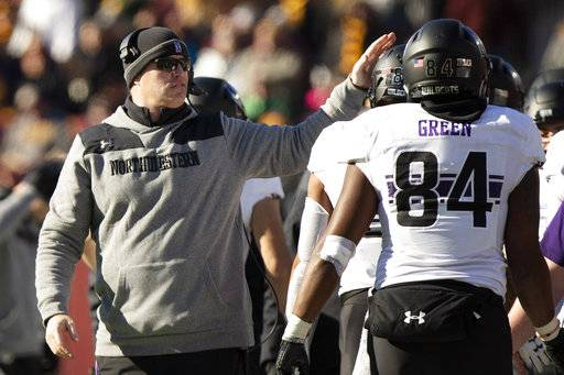 Northwestern head coach Pat Fitzgerald pats Northwestern wide receiver Ramaud Chiaokhiao-Bowman on the helmet during an NCAA college football game against Minnesota, Saturday, Nov. 17, 2018, in Minneapolis. Northwestern won 24-14. (AP Photo/Stacy Bengs)