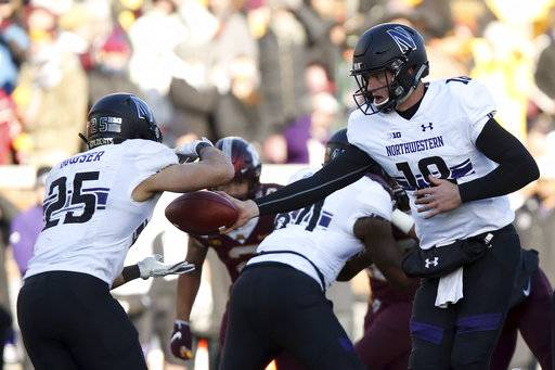 Northwestern quarterback Clayton Thorson hands the ball off to running back Isaiah Bowser during an NCAA college football game against Minnesota, Saturday, Nov. 17, 2018, in Minneapolis. Northwestern won 24-14.