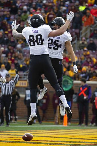 Northwestern running back Isaiah Bowser (25) celebrates with teammate wide receiver Trey Pugh after Bowser scored a touchdown against Minnesota during an NCAA college football game Saturday, Nov. 17, 2018, in Minneapolis.
