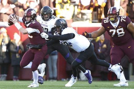 Minnesota quarterback Tanner Morgan, left, avoids a sack by Northwestern's Ben Oxley during an NCAA college football game Saturday, Nov. 17, 2018, in Minneapolis. Northwestern won 24-14.