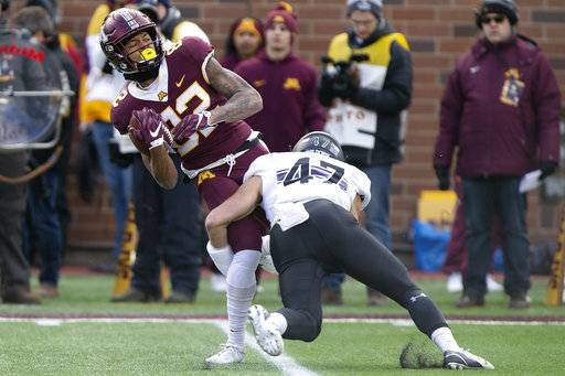Minnesota wide receiver Demetrius Douglas holds onto the ball against Northwestern's Joe Bergin during an NCAA college football game Saturday, Nov. 17, 2018, in Minneapolis.