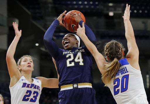 Notre Dame's Arike Ogunbowale, center, goes to the basket between DePaul's Dee Bekelja, left, and Kelly Campbell during the first half of an NCAA college basketball game, Saturday, Nov. 17, 2018, in Chicago. (AP Photo/Jim Young)