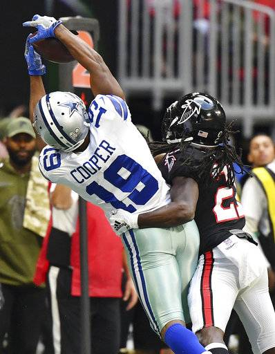 Dallas Cowboys wide receiver Amari Cooper (19) makes the catch against Atlanta Falcons cornerback Desmond Trufant (21) during the second half of an NFL football game, Sunday, Nov. 18, 2018, in Atlanta.