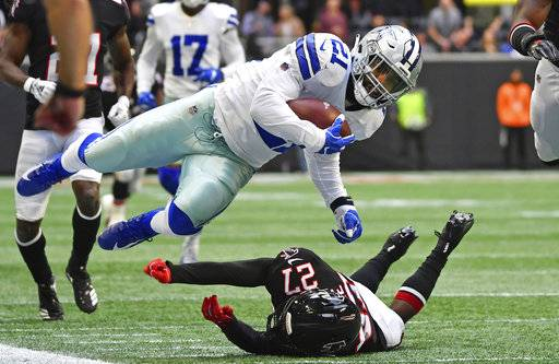 Dallas Cowboys running back Ezekiel Elliott (21) is tripped by Atlanta Falcons strong safety Damontae Kazee (27) during the first half of an NFL football game, Sunday, Nov. 18, 2018, in Atlanta.
