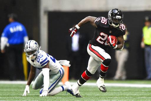 Atlanta Falcons running back Tevin Coleman (26) runs past Dallas Cowboys free safety Xavier Woods (25) during the second half of an NFL football game, Sunday, Nov. 18, 2018, in Atlanta.